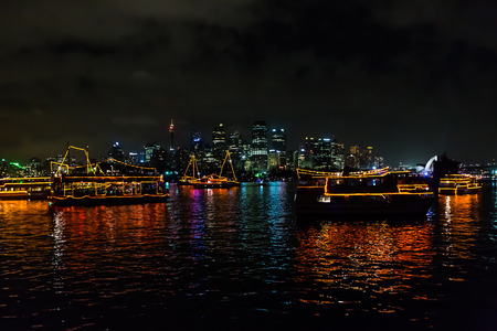 Reflecting boats in Sydney bay waiting for fireworks to celebrate the new year 2015, shot from a boat in a very windy and cloudy sky.  View of Opera House theater and city skyline from the sea.
