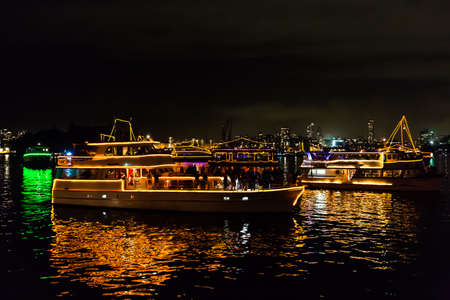 Reflecting boats in Sydney bay waiting for fireworks to celebrate the new year 2015, shot from a boat in a very windy and cloudy sky.  View of city skyline from the sea. Stock Photo