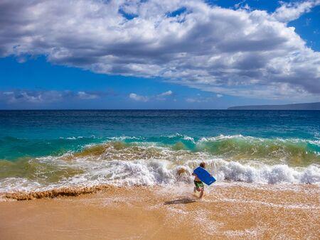 bodyboarding: Young boy runs on sand making bodyboarding, Big Beach, Maui in Hawaii, America.