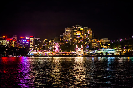 after midnight: Midnight party with a lot of people at amusement park in Sydney with skyline reflecting in the bay after the midnight fireworks of the new years eve 2015, shot from a boat.