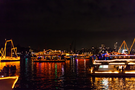 after midnight: Parade of Boats reflecting in Sydney bay after the midnight fireworks of the new years eve 2015, shot from a boat. city skyline in the background. Stock Photo