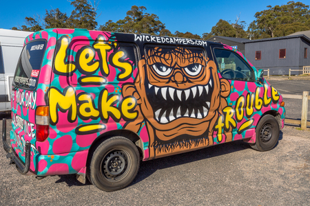 airbrushing: Sydney, Australia - January 9, 2015: Hippie van with Lets Make Trouble airbrushing hand made. Typical campers from Australian company: Wickedcampers.