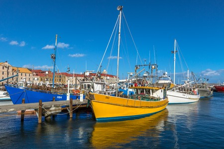 docked: Hobart, Tasmania, Australia - January 16, 2015: Fishing Boats docked at the wooden jetty in Hobart Harbour, Franklin Wharf