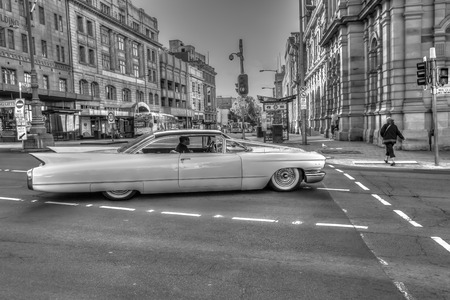 vintage: Hobart, Tasmania, Australia - January 16, 2015: Urban scenery in town as retro-style, black and white. A luxury vintage Cadillac running through streets of historic town.