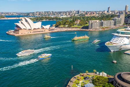 Sydney, Australia - December 29, 2014: center skyline scenery with Opera House, Royal Botanic Gardens, Circular Quay, harbor with huge transoceanic ship, Sydney Tower
