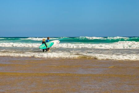 surfers: Phillip Island, Victoria, Australia - January 4, 2015: Two surfers holding surfboards at Woolamai Beach, Cape Woolamai State Faunal Reserve in summer Editorial