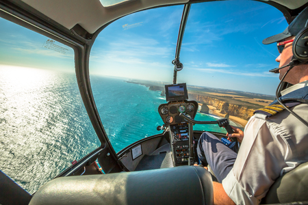 Port Campbell National Park, Victoria, Australia - January 6, 2015: Closeup of the cockpit of a helicopter and pilot who performs a scenic flight over the Twelve Apostles and the shipwreck coast