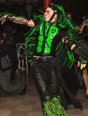dj boy: Modena, Italy - September 21, 2014:Cyber dancer boy in black and fluorescent green dancing, during event:  Dynamika Trauma, music by Dj Slimer.
