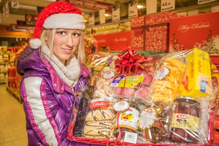 marmelade: Bologna, Italy - December 13, 2014: Woman showing typical italian nationwide food products in for sale only during Christmas weeks. Pasta, Lasagne, regional bisquists, marmelade, mustard, cold cuts