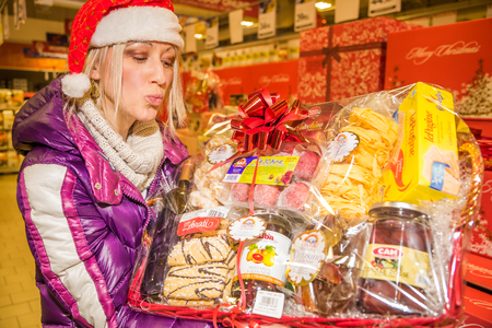 christmas paste: Bologna, Italy - December 13, 2014: Woman showing typical italian nationwide food products in for sale only during Christmas weeks. Pasta, Lasagne, regional bisquists, marmelade, mustard, cold cuts