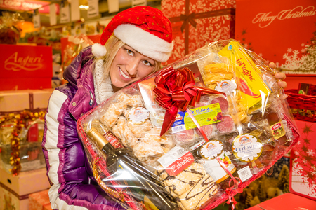 christmas paste: Bologna, Italy - December 13, 2014: Woman showing typical italian nationwide food products in for sale only during Christmas weeks: marmelade, mustard, cold cuts, almond paste, pickles, italian wine.