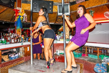 entertain: Lamai, Koh Samui, Thailand - August 3, 2011: Go go bar girl. In These open-air bar girls dancing to entertain tourists on the counter or by a soft lap dance.