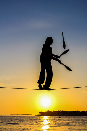 tosses: Key West, Florida, United States - April 13, 2012: A tightrope walker tosses of skittles. Show of street artists that takes place every day at sunset