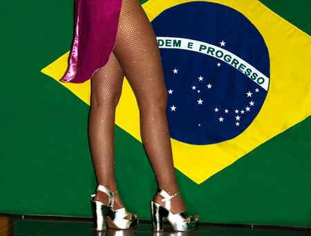 dancer legs: Brazilian dancer legs in high heels shoes and fishnet stockings on Brazili flag background. Stock Photo