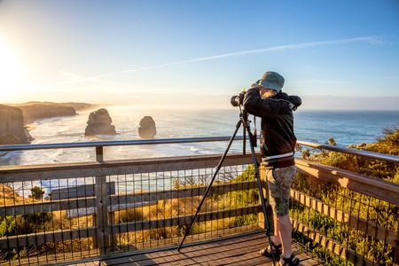 people  camera: Nature australian photographer taking pictures at sunset With His tripod and wide angle chamber to the Twelve Apostles in the state of Victoria in Australia.