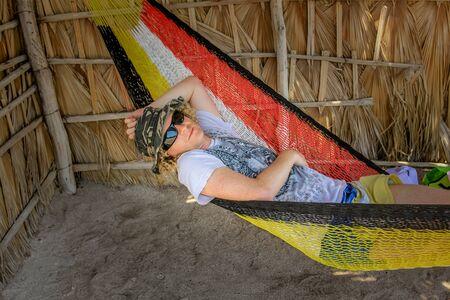relaxes: Hombre tur�stico se relaja en una hamaca. Un Concepci�n Baja California Sur, M�xico.