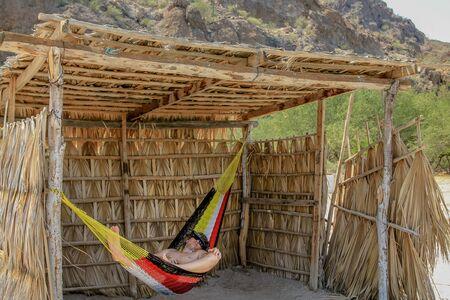 Tourist man relaxes on a hammock. A Conception Baja, California Sur, Mexico. Stock Photo