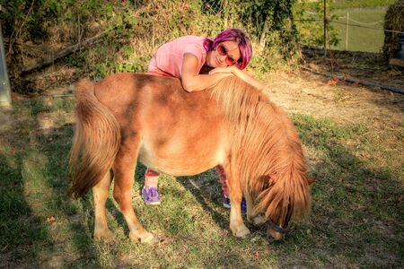 shetland pony: Young woman hugging a Shetland pony in the countryside. Stock Photo