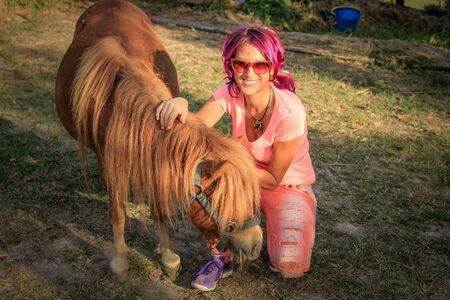 shetland pony: Young and smiling woman hugging a Shetland pony in the countryside. Stock Photo