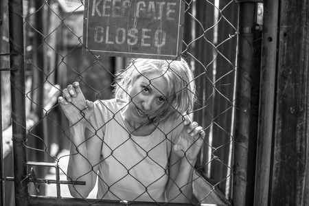 insane insanity: Psychotic woman in the cage in black and white, keep gate closed.