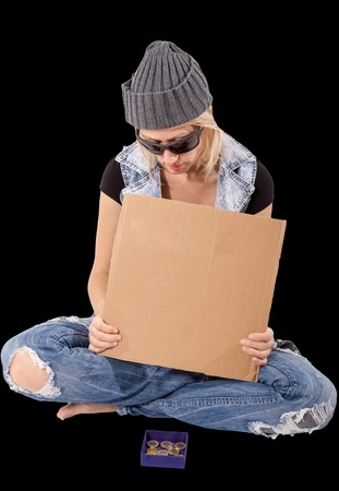 poorness: Sitting homeless woman is holding a blank cardboard while begging. Pure black backgroung.