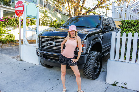 Attractive blond woman stood next to a 4x4 car in Miami, Florida, U.S.A. Stock Photo