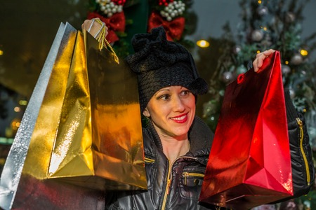 compras compulsivas: Portrait of a happy woman holding shining shopping bags for Christmas.