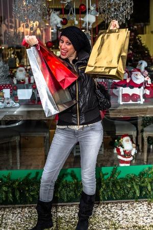 avid: Cravings woman holding shining shopping bags during Christmas sales at shop window. Stock Photo
