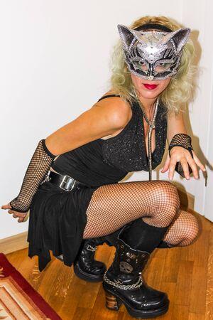 bas r�sille: Attractive femme en robe noire maigre, r�sille, bas, bottes plate-forme et de l'argent masque de chat � genoux sur le plancher en bois poli � la f�te d'Halloween. .