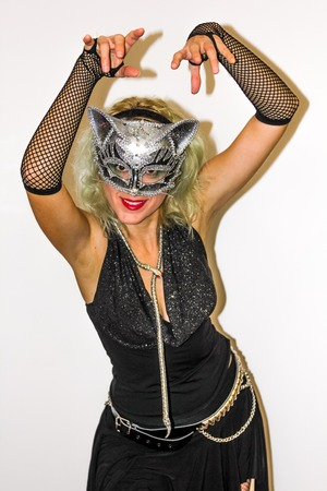 skimpy: Attractive woman in skimpy black dress, fishnet stockings and silver cat mask for Halloween party.