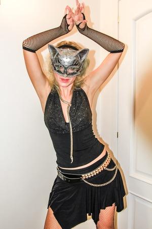 bas r�sille: Jolie femme dans �triqu�s robe noire, bas r�sille et d'argent masque de chat pour la f�te d'Halloween.