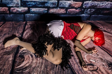 prostitute: Dead woman prostitute laying down on the floor after assault. Stock Photo