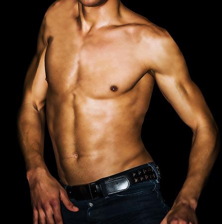 Masculino atractivo en pantalones vaqueros que muestran abdominales sobre fondo negro. Foto de archivo - 42808669