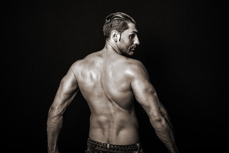 muscularity: Rear view of a muscular young man with a bare torso in black and white color on black background. Stock Photo