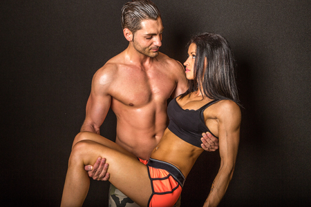 sports gear: Portrait of fit, muscular, athletic couple, standing close together, wearing only sports gear on black background.