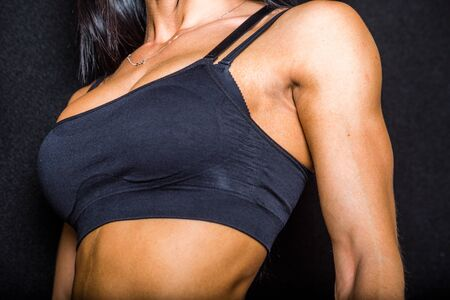 pectorals: Body of a female bodybuilder showing her pectoral muscles. on black background.