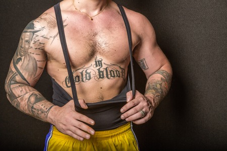 bare chested: Bologna, Italy - June 21, 2014: Half body portrait of a bare chested bodybuiler man flexing his muscles and showing artistic tatoo during a private exhibition in the city gym