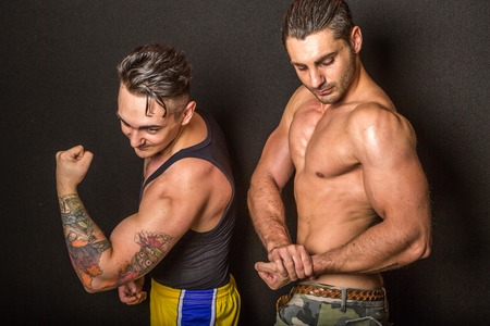 bare chested: Bologna, Italy - June 21, 2014: Two bare chested bodybuiler men flexing muscles and showing artistic tatoo during a private exhibition in the city gym