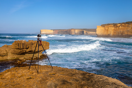 ard: Camera on a tripod ready to shoot a landscape scenery at Loch Ard Gorge, part of Port Campbell National Park, Victoria, Australia. Camera in image is a Canon.