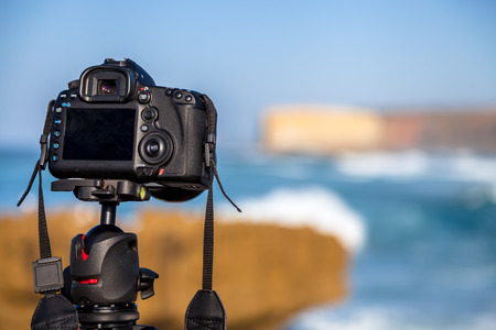 Closeup of a camera on a tripod outdoors. Camera is Canon. background Landscape out of focus. Concept of hobbies, work, travel, tourism and professional photography. Stock Photo