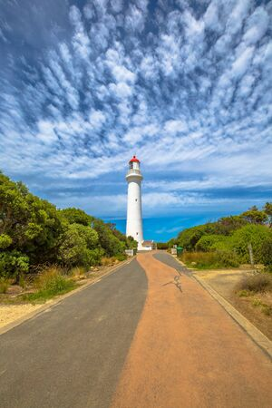 split road: Split Point Lighthouse with blue sky located in Aireys Inlet on the Great Ocean Road, Victoria, Australia.