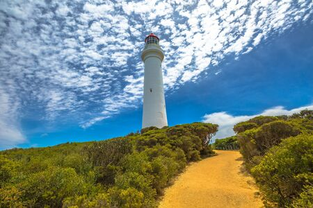 split road: Split Point Lighthouse with blue sky located in Aireys Inlet on Great Ocean Road, Victoria, Australia. .