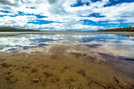 tasman: Wild landscapes with clouds reflected in the water, on Nubeena Road, near Koonya in Tasman Peninsula in Tasmania, Australia.