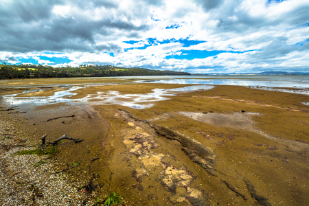 tasman: Nubeena Road, wild Koonya drammatic landscape with cloudy sky and rocky beach in the Tasman Peninsula in Tasmania, Australia.