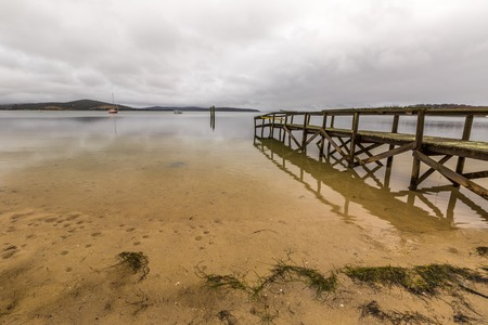 helens: Wooden pier reflects in Georges Bay beach in St Helens, the most important city on the East Coast, Tasmania, Australia. Concept of simplicity, of peace, calm and tranquility.