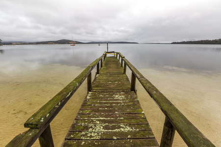 helens: Dock in the cloudy sky in Georges Bay beach in St Helens, the most important city on the East Coast, Tasmania, Australia. Concept of simplicity, purpose, direction and infinity.