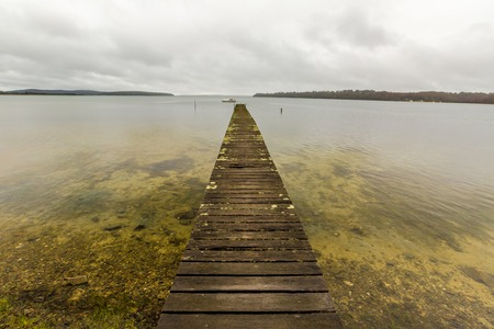 helens: Mystic cloudy landscape and wooden jetty in Georges Bay, St Helens, the most important city on the East Coast, Tasmania, Australia. Concept of simplicity, purpose, direction and infinity. Stock Photo