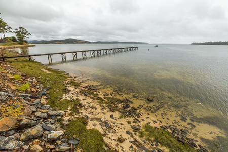 helens: Cloudy landscape and wooden jetty in Georges Bay, St Helens, the most important city on the East Coast, Tasmania, Australia.