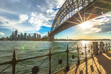 sydney: Spectacular Sydney Skyline at sunset. Walking on the path that leads beneath the Sydney Harbour Bridge, New South Wales, Australia.