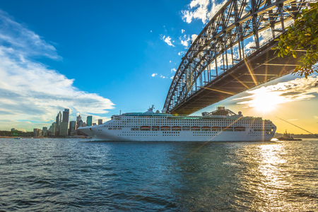 Cruise ship under Sydney Harbour Bridge at sunset with skyline, New South Wales, Australia. Stok Fotoğraf